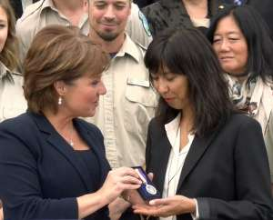 Phare's fiance Kimi Hawkes accepting the medal from Premier Christy Clark